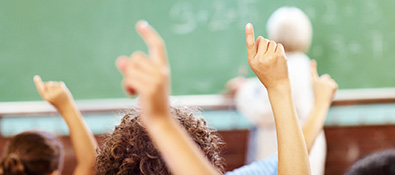 k12 educators - students with hands raised