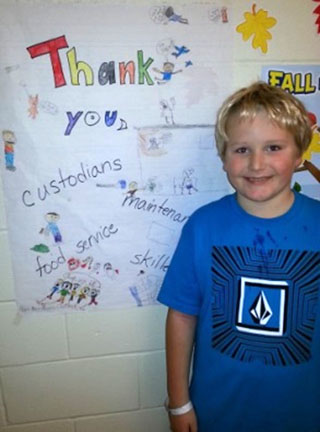SRP Recognition - Miller Mietus, third-grader at Scribner Road Elementary School, with a poster he and classmates completed to thank SRPs in Mrs. Sherrill Moon's class.