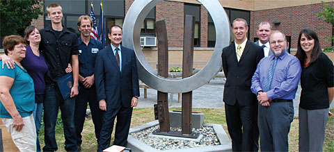 High school junior Dakoda Ball, third from left, helps unveil the Springville-Griffith Institute school district 9/11 memorial sculpture. Photo by Dennis Stierer.