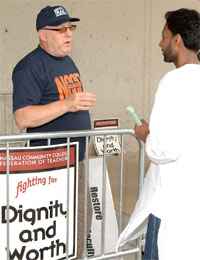 Nassau CCFT member Richard Newman, left, discusses the union's concerns with graduating student Ghouse Hameed.