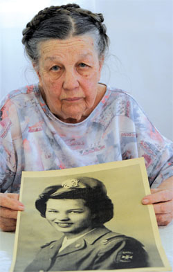 Anne Kakos holds a photo of herself as a Cadet Nurse during World War II.