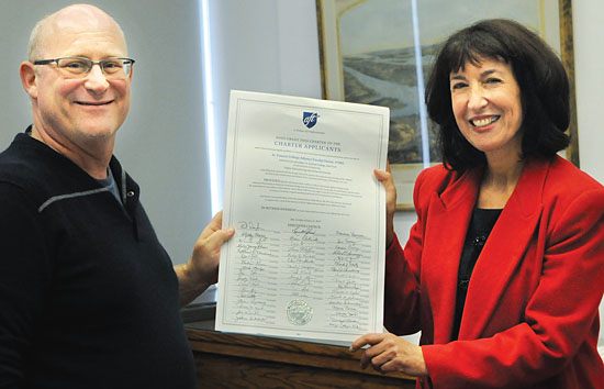 Judy Sandler, a NYSUT labor relations specialist, presents Howard Skrill, interim treasurer of St. Francis College Adjunct Faculty Union, with the new unit's charter.