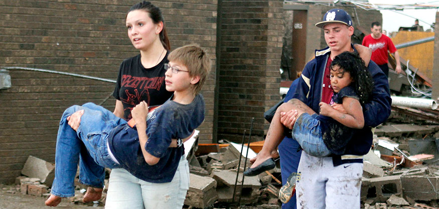 Teachers carry children away from Briarwood Elementary school after a tornado destroyed the school in south Oklahoma City, Okla, Monday, May 20, 2013. Near SW 149th and Hudson. (AP Photo/ The Oklahoman, Paul Hellstern)