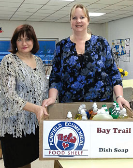 Penfield teachers Chris McGovern and Sue Mietus prepare items for donation to the food shelf.