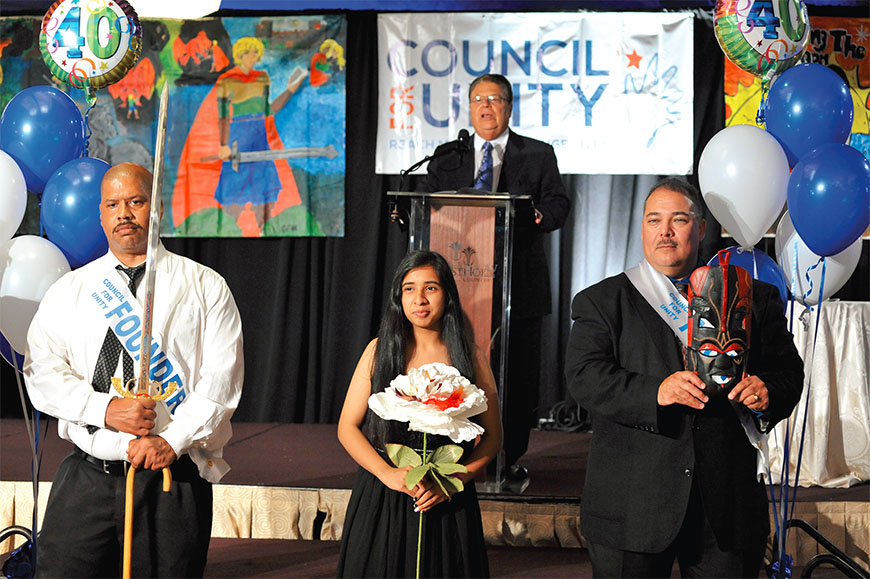 From left: Sword bearer Marc Grant, John Dewey HS student Zaineb Naseem and mask bearer James Concepcion at the Council for Unity induction ceremony, where students are celebrated for their commitment to respect, unity and making a positive impact in their schools and communities. CFU founder Bob De Sena is at the podium. Photo by Maria R. Bastone.