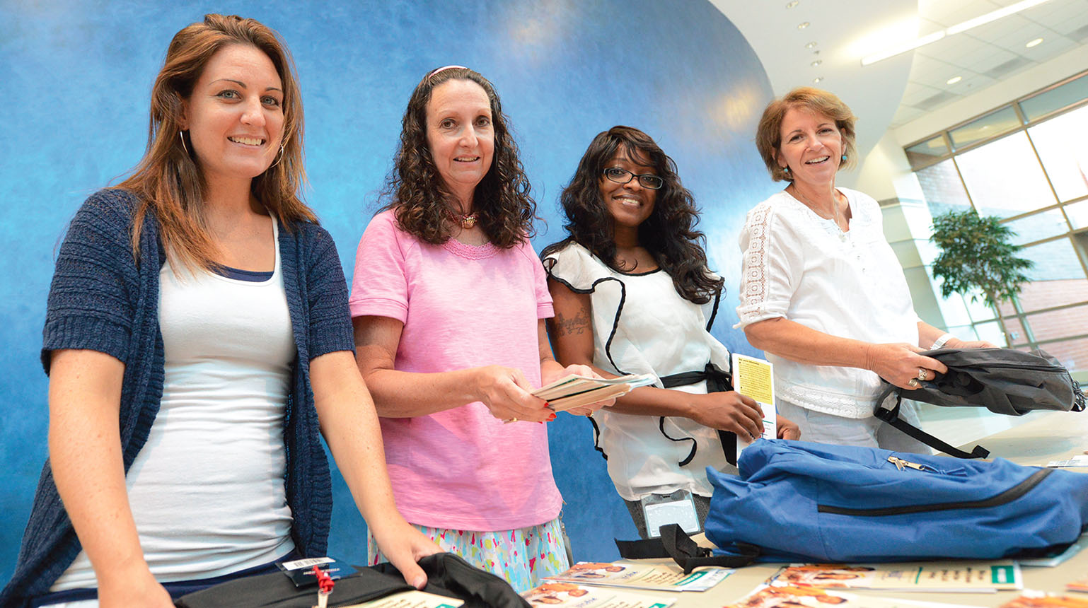 NYSUT staff members, from left, Lindsay O'Sullivan, Lori Agnew, Swinka Richards and Helen Vickery help stuff 1,200 backpacks with school supplies and donated books from the NYSUT-AFT-First Book project.