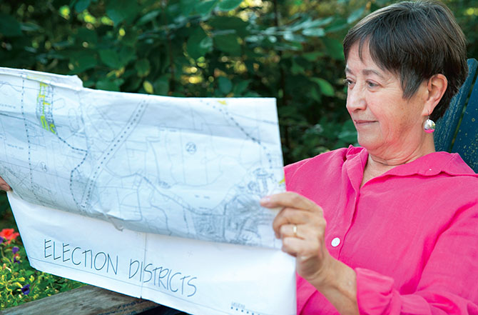 Retired teacher Janet Wheile checks a map outlining election districts in Saratoga County. Photo by Marty Kerins Jr.