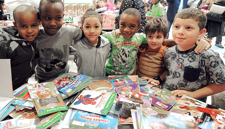 Students at Frazer Pre-K–8 School in Syracuse receive their First Books in a December giveway for the holidays. More than 2,000 books were distributed. Photo by El-Wise Noisette.