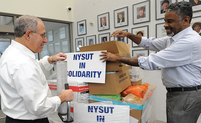 NYSUT President Andy Pallotta and First Vice President J. Philippe Abraham prepare to load supplies donated for disaster relief.